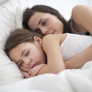 Mother holding her sleeping daughter in bed