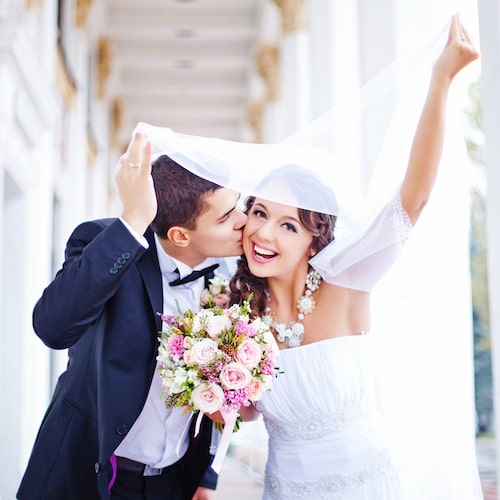 A bride and groom on their wedding day and smiling while holding flowers