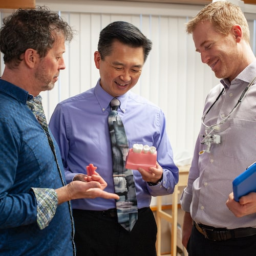 Dr. Hill, Dr. Garrett, and Dr. Wang all talking to each other while holding dental props