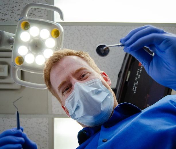 Dr. Garrett looking down at the camera while wearing a dental mask and holding dental tools