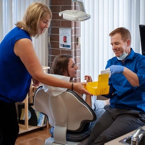 Dr. Garrett and a dental assistant talking to a patient who is sitting in a treatment chair