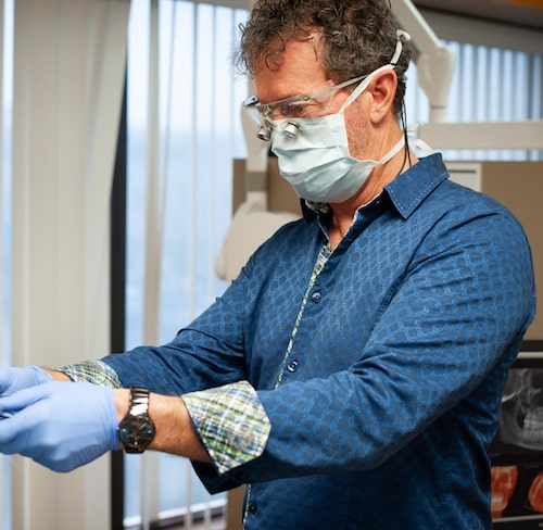 Dr. Hill in a blue shirt and wearing a dental mask