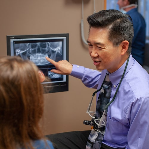 Dr. Wang talking to a patient while pointing at a digital x-ray on a screen