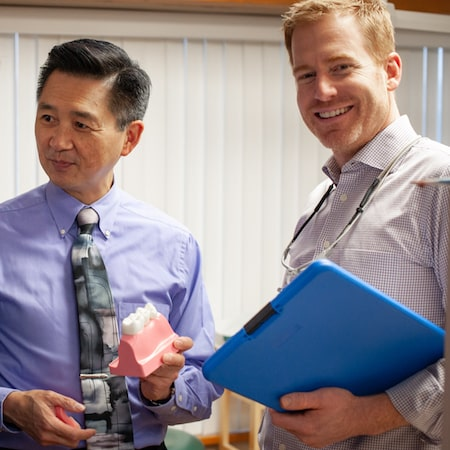 Dr. Wang and Dr. Garrett standing next to each, Dr. Garrett holding a blue folder and smiling