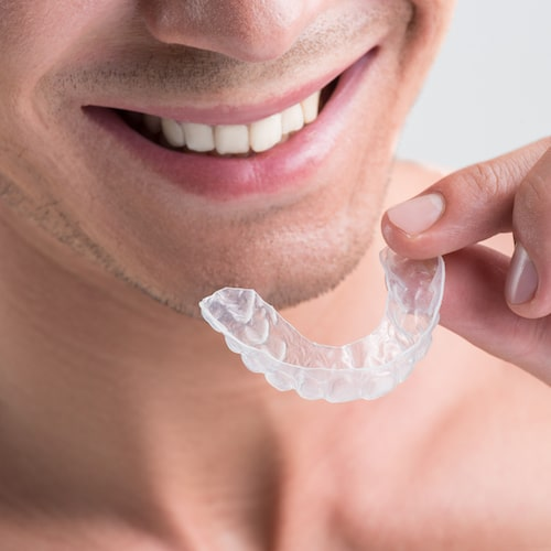 A man smiling and holding a clear aligner