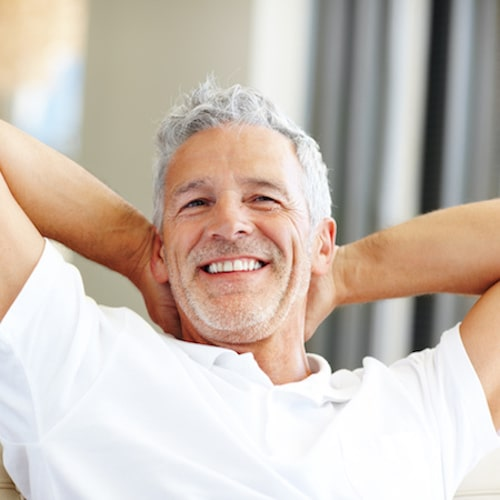 Older man sitting back on a sofa with his hands behind his head