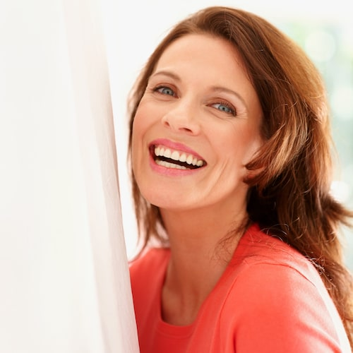 Mature woman leaning against a white wall and laughing
