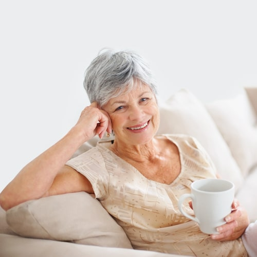 Mature woman with short grey hair sitting on a sofa, holding a cup, and smiling