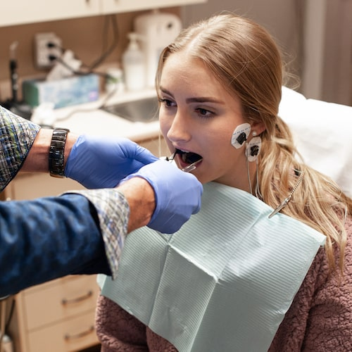 Young girl in treatment chair wearing an office bib and having a dental exam