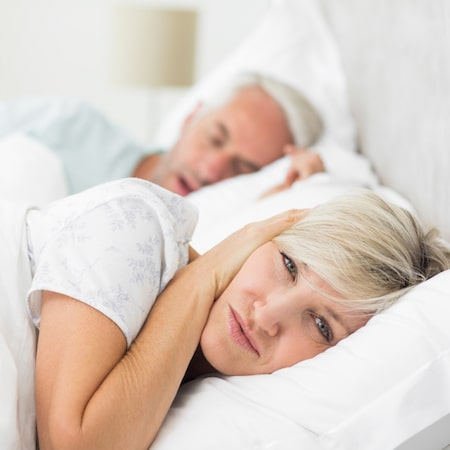 Couple in a bed, women in front with her hands over her ears and man behind her snoring