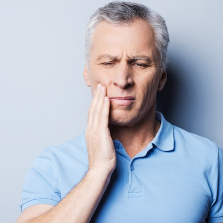 Man in a light blue top holding the side of his jaw in pain