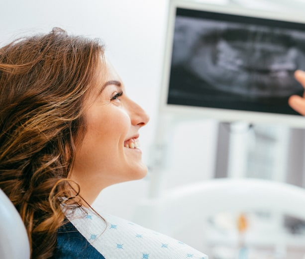 Profile of a women smiling in a dental chair with a digital screenshot in the background