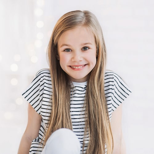 Young girl with a black and white striped top and long light brown hair smiling