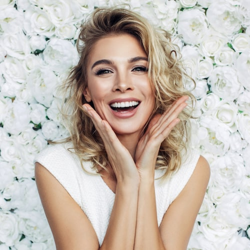 A woman smiling in front of a white flower wall with shoulder length blond hair