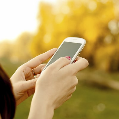 Female holding a mobile phone with an autumnal background