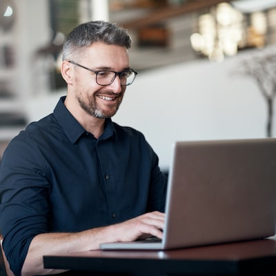 Man with glasses using a laptop in a public place