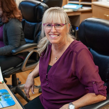 A member of our team smiling while she sits in a chair